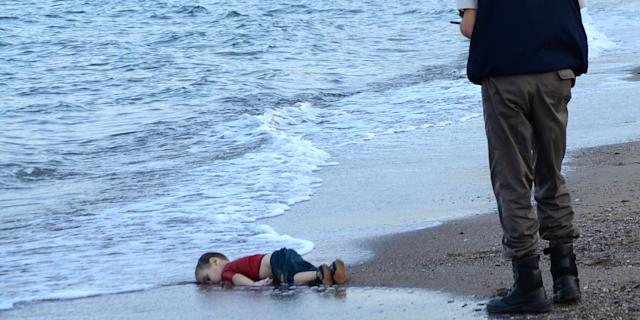 A Turkish police officer stands next to a migrant child's body off the shores in Bodrum, southern Turkey, on September 2, 2015 after a boat carrying refugees sank while reaching the Greek island of Kos. The child's name was Alan Kurni (born Aylan Shenu). Photo: NILUFER DEMIR/AFP via Getty Images