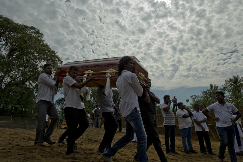 Relatives carry a coffin for burial during a mass burial for Easter Sunday bomb blast victims in Negombo, Sri Lanka, Wednesday, April 24, 2019. (AP Photo/Gemunu Amarasinghe)