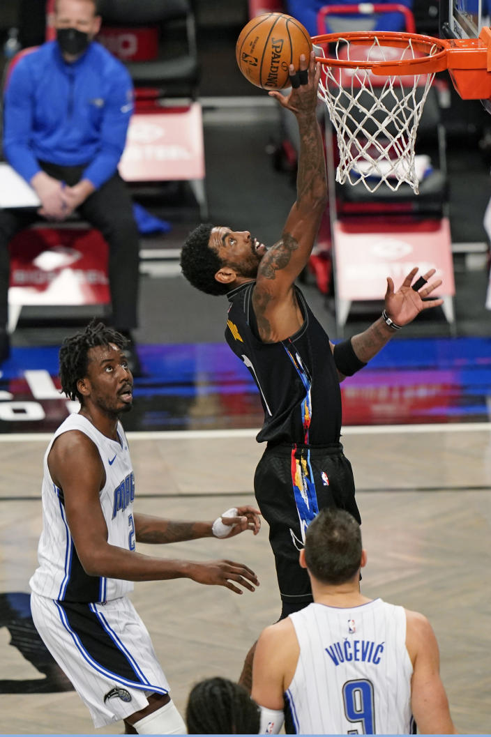Brooklyn Nets guard Kyrie Irving (11) tries to tip the ball in as Orlando Magic forward Al-Farouq Aminu (2) and center Nikola Vucevic (9) look on during the first quarter of an NBA basketball game, Thursday, Feb. 25, 2021, in New York. (AP Photo/Kathy Willens)