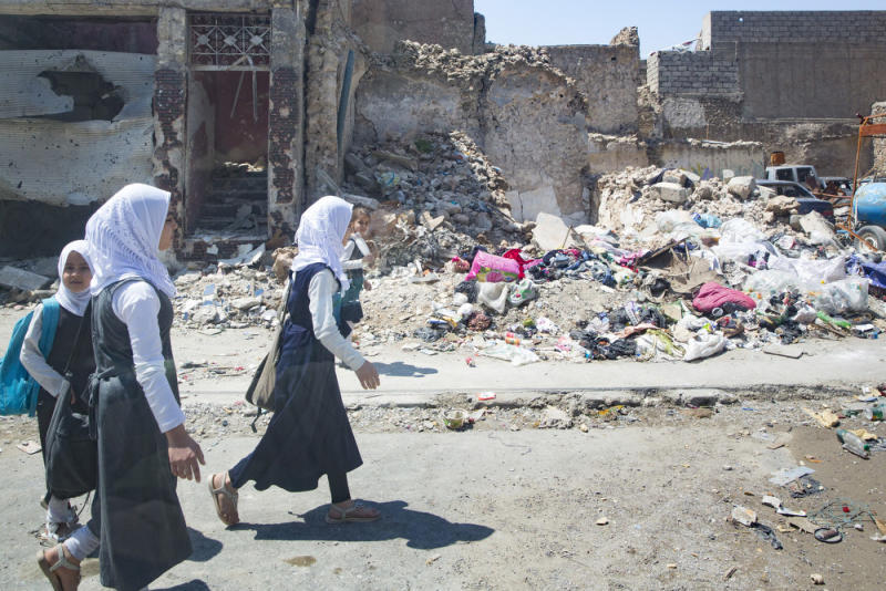 MOSUL, IRAQ - April 24: Girls in school uniforms walk on a street passing ruined houses in the destroyed old town in Mosul on April 24, 2018 in MOSUL, IRAQ. (Photo by Ute Grabowsky/Photothek via Getty Images)