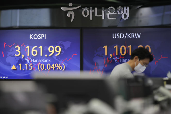 A currency trader walks by the screens showing the Korea Composite Stock Price Index (KOSPI), left, and the foreign exchange rate between U.S. dollar and South Korean won at the foreign exchange dealing room in Seoul, South Korea, Friday, Jan. 22, 2021. Asian stock markets retreated Friday after a resurgence of coronavirus infections in China and a rise in cases in Southeast Asia. (AP Photo/Lee Jin-man)