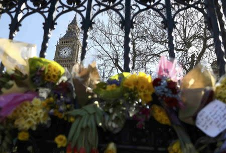 Floral tributes are tied to a fence in Parliament Square following the attack in Westminster earlier in the week, in central London
