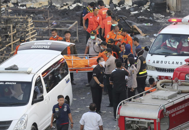 <p>Police officers and rescuers carry a body at the site of an explosion at a firecracker factory in Tangerang, on the outskirts of Jakarta, Indonesia, Thursday, Oct. 26, 2017. The explosion and raging fire killed a number of people and injured dozens, police said. (Photo: Tatan Syuflana/AP) </p>