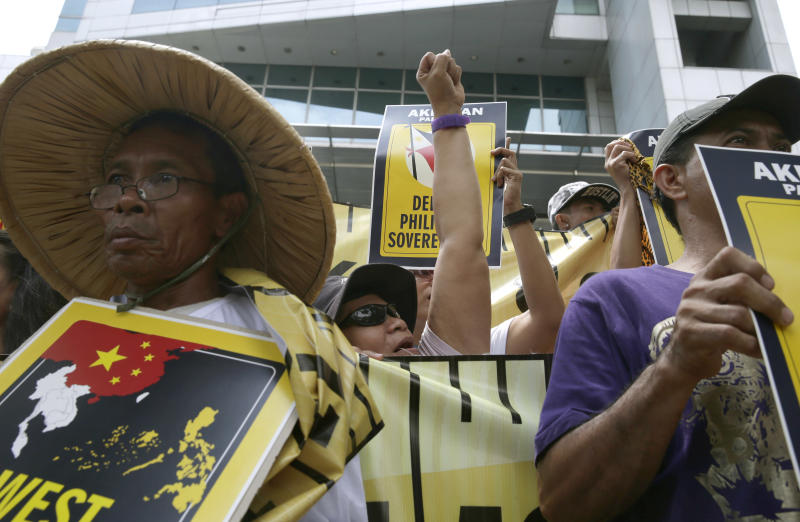 Protesters shout slogans during a rally outside the Chinese consulate at the financial district of Makati city east of Manila, Philippines Wednesday, April 2, 2014. Dozens of Filipino left-wing activists protested at China's consulate to protest the blocking by Chinese coast guard ships of a Philippine supply boat near a disputed shoal in the South China Sea. (AP Photo/Bullit Marquez)