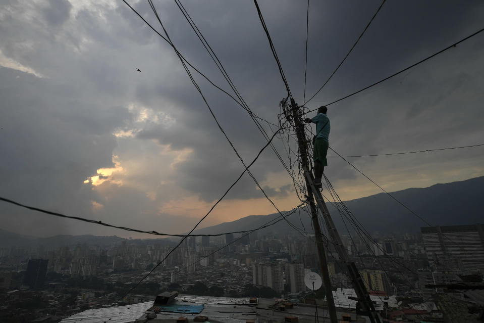 A man fixes power lines in the San Agustin neighborhood of Caracas, Venezuela, Sunday, May 17, 2020. President Nicolas Maduro is relaxing quarantine measures over the weekend by allowing children and older adults out of their homes for a few hours each day. (AP Photo/Matias Delacroix)