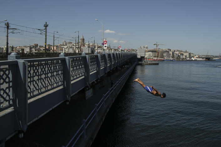 Backdropped by Galata Tower, a youth jumps from the Galata Bridge into the Golden Horn leading to the Bosphorus Strait separating Europe and Asia, in Istanbul, Friday, May 14, 2021. Turkey is in the final days of a full coronavirus lockdown and the government has ordered people to stay home and businesses to close amid a huge surge in new daily infections. But millions of workers are exempt and so are foreign tourists. Turkey is courting international tourists during an economic downturn and needs the foreign currencies that tourism brings to help the economy as the Turkish lira continues to sink. (AP Photo/Emrah Gurel)
