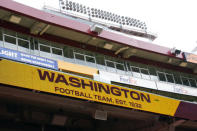 Fedex Field scoreboard displays the Washington Football Team name during warmups before the start of a NFL football game between Washington Football Team and Philadelphia Eagles, Sunday, Sept. 13, 2020, in Landover, Md. Washington has dumped its 86-year-old team name, handed over an investigation into workplace misconduct to the NFL, seen minority owners and Dan Snyder battle it out in court, coach Ron Rivera battle a form of skin cancer and reached the playoffs on the arm of a quarterback who hadn't played in two years because of an injury that looked career-threatening. All in a few months' work for arguably the biggest soap opera in professional sports with a playoff game against Tom Brady up next. (AP Photo/Susan Walsh)