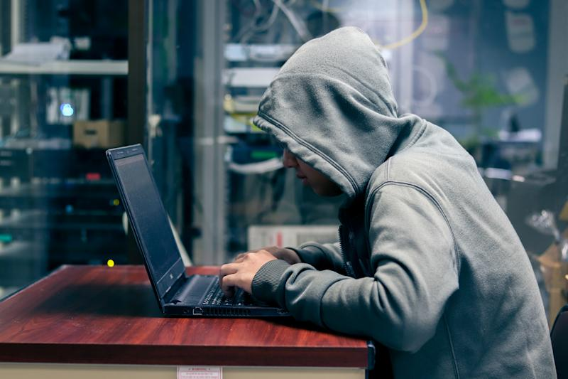 Hacker is Using Computer for Organizing Massive Data Breach Attack on Corporate Servers. Their Hideout is Dark, Neon Lit