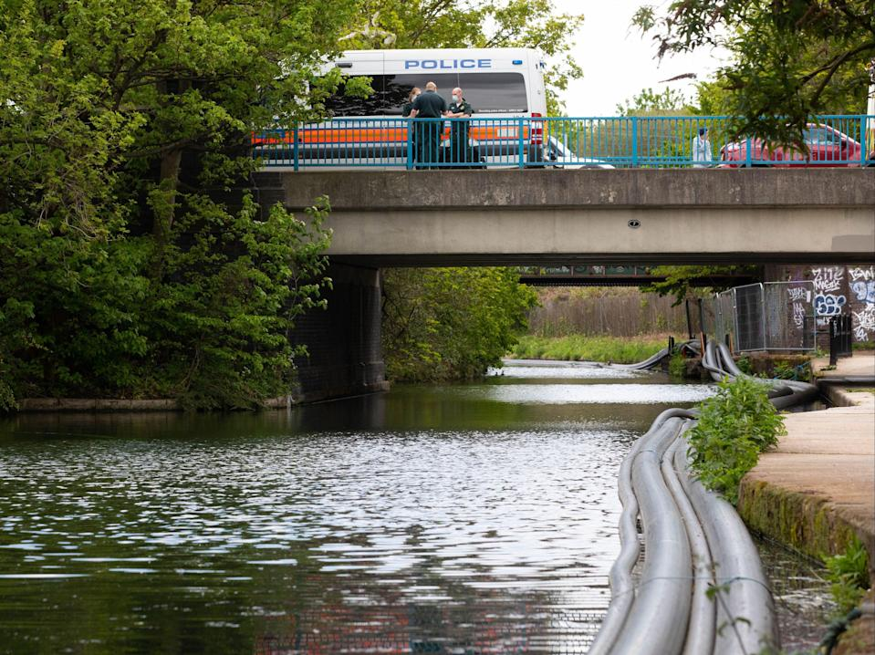 <p>Police officers on scene at the Grand Union Canal near Old Oak Lane in northwest London.</p> (PA)
