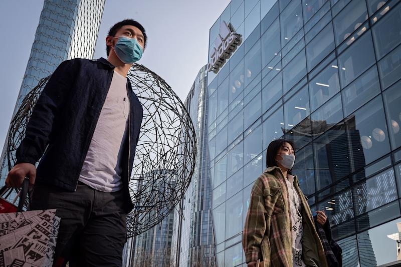 A woman and a man wearing facemasks as a preventive mesure against the COVID-19 coronavirus walk outside a shopping mall in Beijing on March 11, 2020. - Mainland China, where all people arriving in Beijing from abroad will be placed in quarantine for two weeks, has 80,778 cases, with 3,158 deaths and 61,475 people cured. (Photo by NICOLAS ASFOURI / AFP) (Photo by NICOLAS ASFOURI/AFP via Getty Images)
