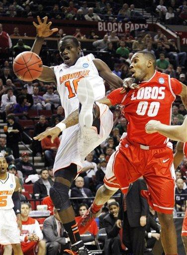Louisville center Gorgui Dieng, left, and New Mexico forward A.J. Hardeman battle for the ball during the first half of their NCAA tournament third-round college basketball game in Portland, Ore., Saturday, March 17, 2012. (AP Photo/Don Ryan)