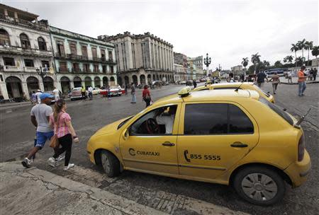 A taxi driver awaits customers in Havana