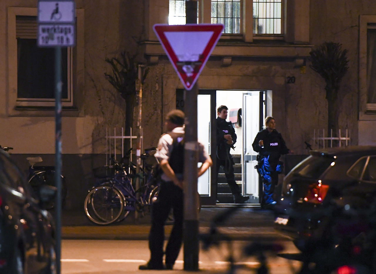 <p>Police officers are seen exiting an appartment building where investigators are searching a flat belonging to a man suspected of having driven a car into a crowd killing two and injuring several others before killing himself at a pedestrian area in Muenster, western Germany on April 7, 2018. (Photo: Patrik Stollarz/AFP/Getty Images) </p>