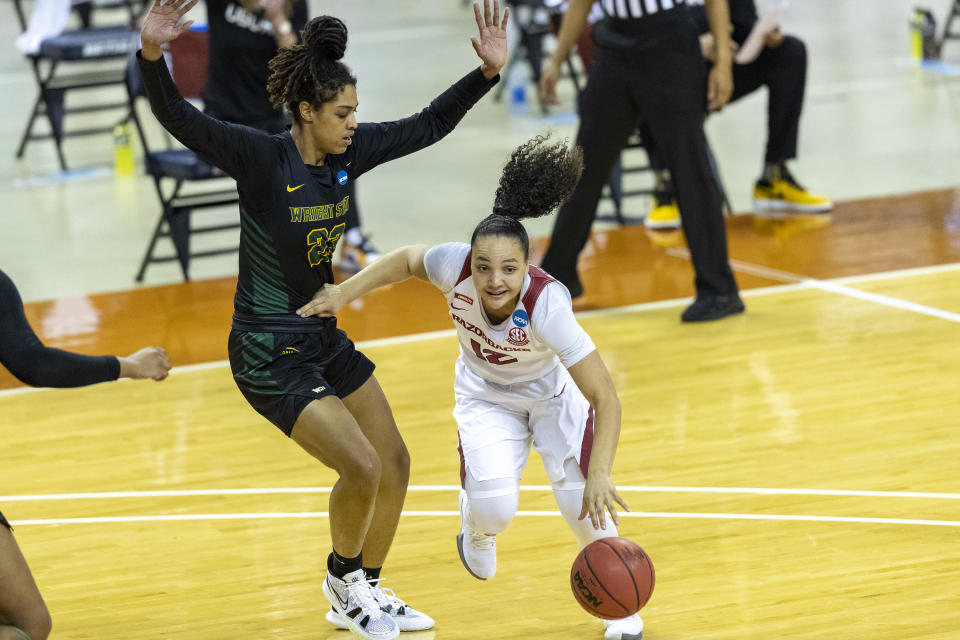 Arkansas guard Destiny Slocum, right, drives around Wright State center Jada Wright, left, during the first half of a college basketball game in the first round of the women's NCAA tournament at the Frank Erwin Center in Austin, Texas, Monday, March 22, 2021. (AP Photo/Stephen Spillman)