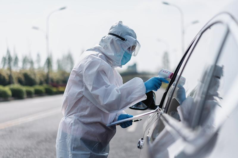 Pictured is a health worker taking somebody's temperature through a car window.