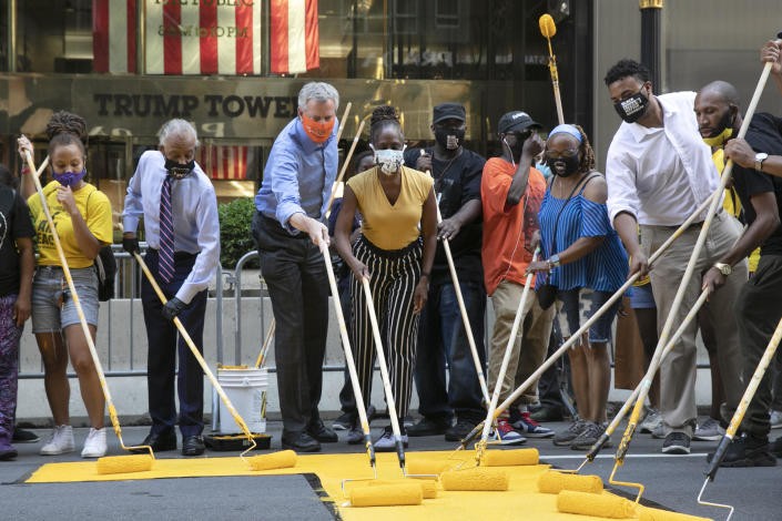 Mayor Bill de Blasio, third from left, participates in painting Black Lives Matter on Fifth Avenue in front of Trump Tower, Thursday, July 9, 2020, in New York. The mayor's wife, Chirlane McCray, is fourth from left and Rev. Al Sharpton is second from left. / Credit: Mark Lennihan / AP