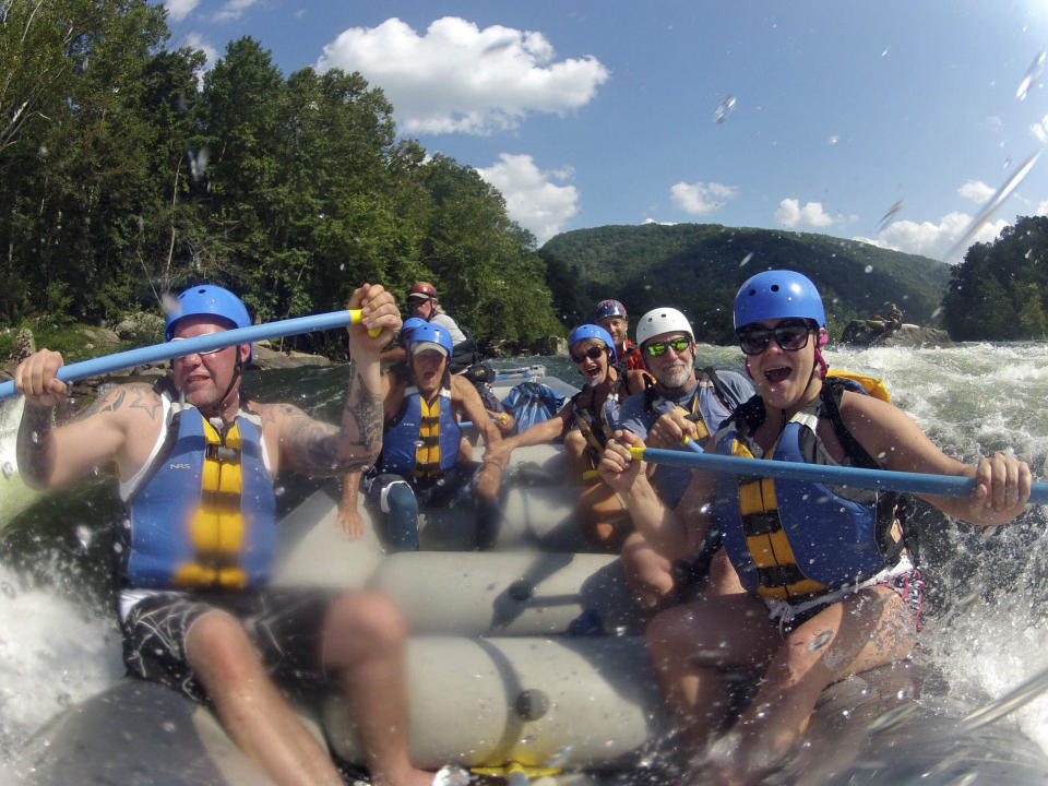 FILE - In this Aug. 30, 2012 file photo whitewater rafters are shown rafting the lower New River Gorge, near Fayetteville, W.Va. A program launched Monday, April 12, 2021, will try to lure outdoor enthusiasts to live and work in West Virginia with enticements of $12,000 cash and free passes for a year for recreation destinations such as whitewater rafting and golf. (Lawrence Pierce/Charleston Gazette-Mail via AP, File)