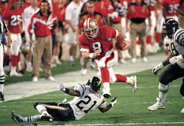 FILE - In this Jan. 29, 1995, file photo, San Francisco 49ers' quarterback Steve Young (8) runs over San Diego's Darrien Gordon (21) for a first down during the first quarter of Super Bowl XXIX at Joe Robbie Stadium in Miami. The NFL became a truly booming business in the 1990s, with multi-billion-dollar TV contracts, expansion to 30 teams, and a late-decade wave of new stadiums. Players began to pick up a bigger share of the wealth, with the dawn of unrestricted free agency. The results on the field were largely dominated by the NFC, with Emmitt Smith and the Dallas Cowboys, Young and the 49ers, and Brett Favre and the Green Bay Packers enjoying the most success. (AP Photo/Andrew Innerarity, File)