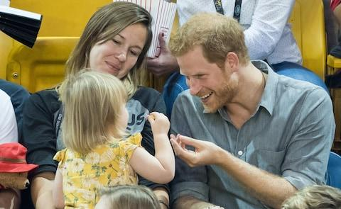 Prince Harry has fun with a toddler at the Invictus Games - Credit: Samir Hussein