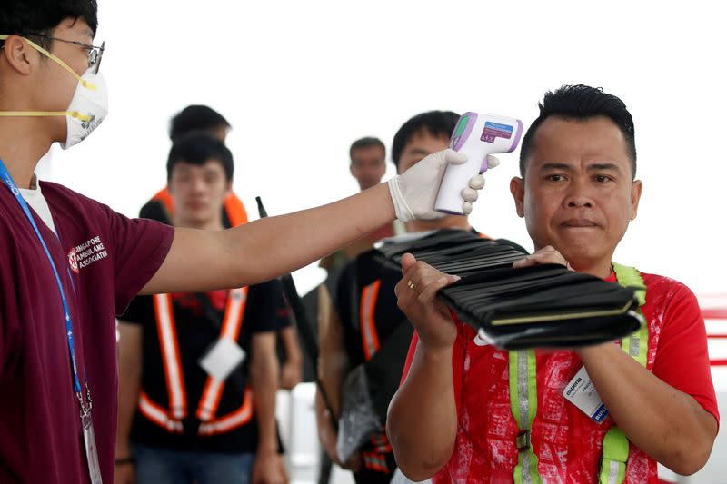 Workers have their temperatures taken at the arrival area during a media preview of the Singapore Airshow in Singapore