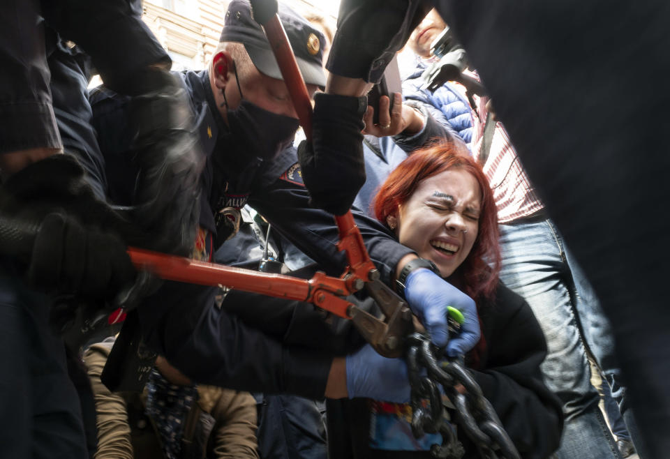 Police try to cut the handcuffs off a woman who handcuffed herself to a fence during a rally supporting Khabarovsk region's governor Sergei Furgal in St.Petersburg, Russia, Saturday, Aug. 1, 2020. Thousands of demonstrators rallied Saturday in the Russian Far East city of Khabarovsk to protest the arrest of the regional governor, continuing a three-week wave of opposition that has challenged the Kremlin. (AP Photo/Dmitri Lovetsky)