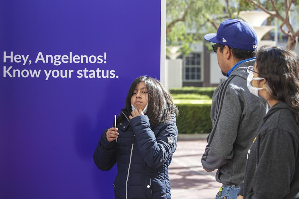 A girl holds a test swab in front of her face next to a sign that says: Hey, Angelenos! Know your status.