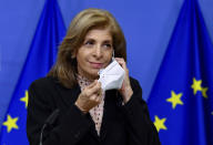 European Commissioner in charge of Health Stella Kyriakides removes her face mask as she gives a statement at the European Commission headquarters in Brussels, Monday, Jan. 25, 2021. The European Union lashed out Monday at the pharmaceutical giant AstraZeneca, accusing the company of failing to deliver the coronavirus vaccine doses to the bloc that it initially promised despite being funded by the bloc to ramp up production. (John Thys/Pool Photo via AP)