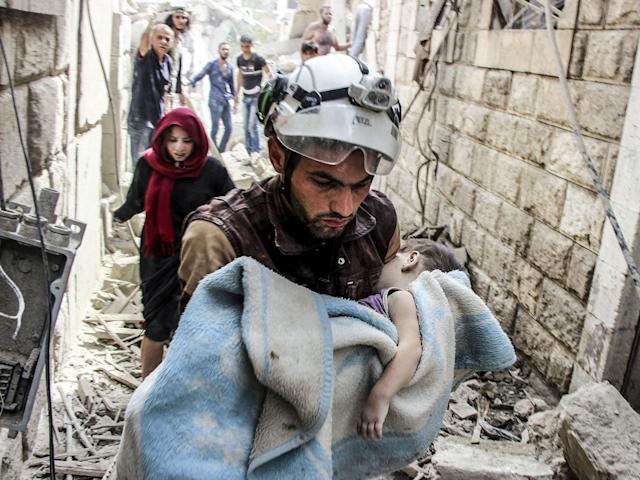 <p>SEPT. 25, 2017 – A search and rescue member holds a baby wrapped with a blanket after Assad Regime's forces carried out air strikes over the de-conflict zone, at the Jisr al-Shughur district of Idlib, Syria. (Photo: Hadi Kharat/Anadolu Agency/Getty Images) </p>