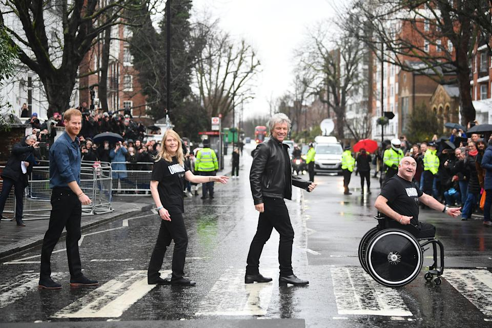 The Duke of Sussex, Jon Bon Jovi and members of the Invictus Games Choir walk on the famous zebra crossing outside the Abbey Road Studios in London.