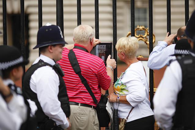 LONDON, ENGLAND - JULY 23: Members of the public gather outside Buckingham Palace to read the easel displaying the announcement of the birth of a son to The Duke and Duchess of Cambridge on July 23, 2013 in London, England. The Duchess of Cambridge has given birth to a baby boy yesterday at 16.24 BST. (Photo by Dan Dennison/Getty Images)