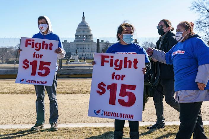 Activists appeal for a $15 minimum wage near the Capitol in Washington, Thursday, Feb. 25, 2021. The $1.9 trillion COVID-19 relief bill being prepped in Congress includes a provision that over five years would hike the federal minimum wage to $15 an hour.