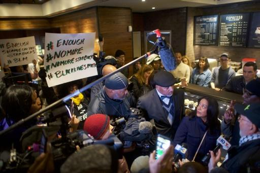 Camille Hymes (C), a Starbucks regional vice-president, addresses media and protestors in a Philadelphia outlet of the coffee chain on April 15, 2018 after the police arrest of two black men sparked outrage and the company apologized