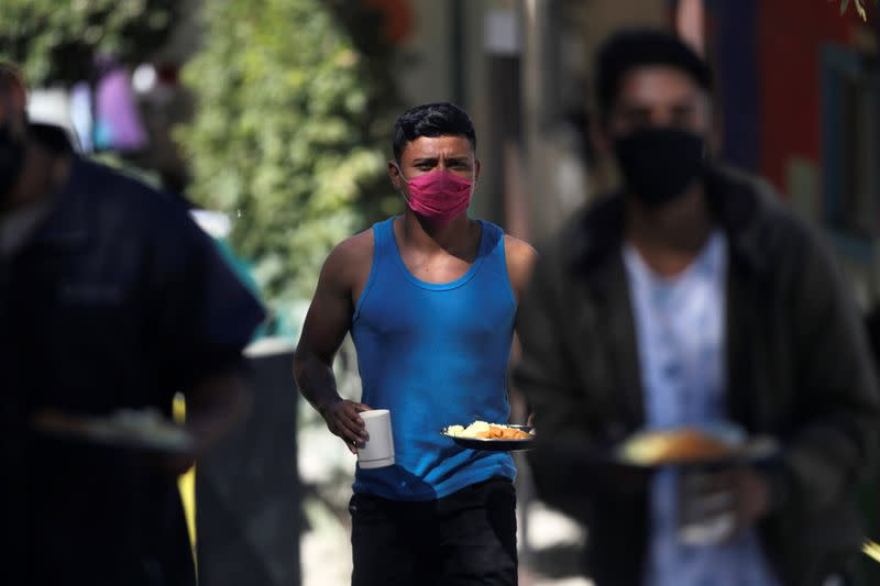 Migrant walks with food in their hands at Posada Belen migrant shelter, before being closed due to an outbreak of the coronavirus disease COVID-19, in Saltillo