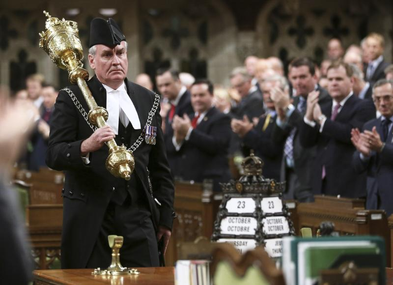 Canada's Sergeant-at-Arms Kevin Vickers is applauded in the House of Commons in Ottawa