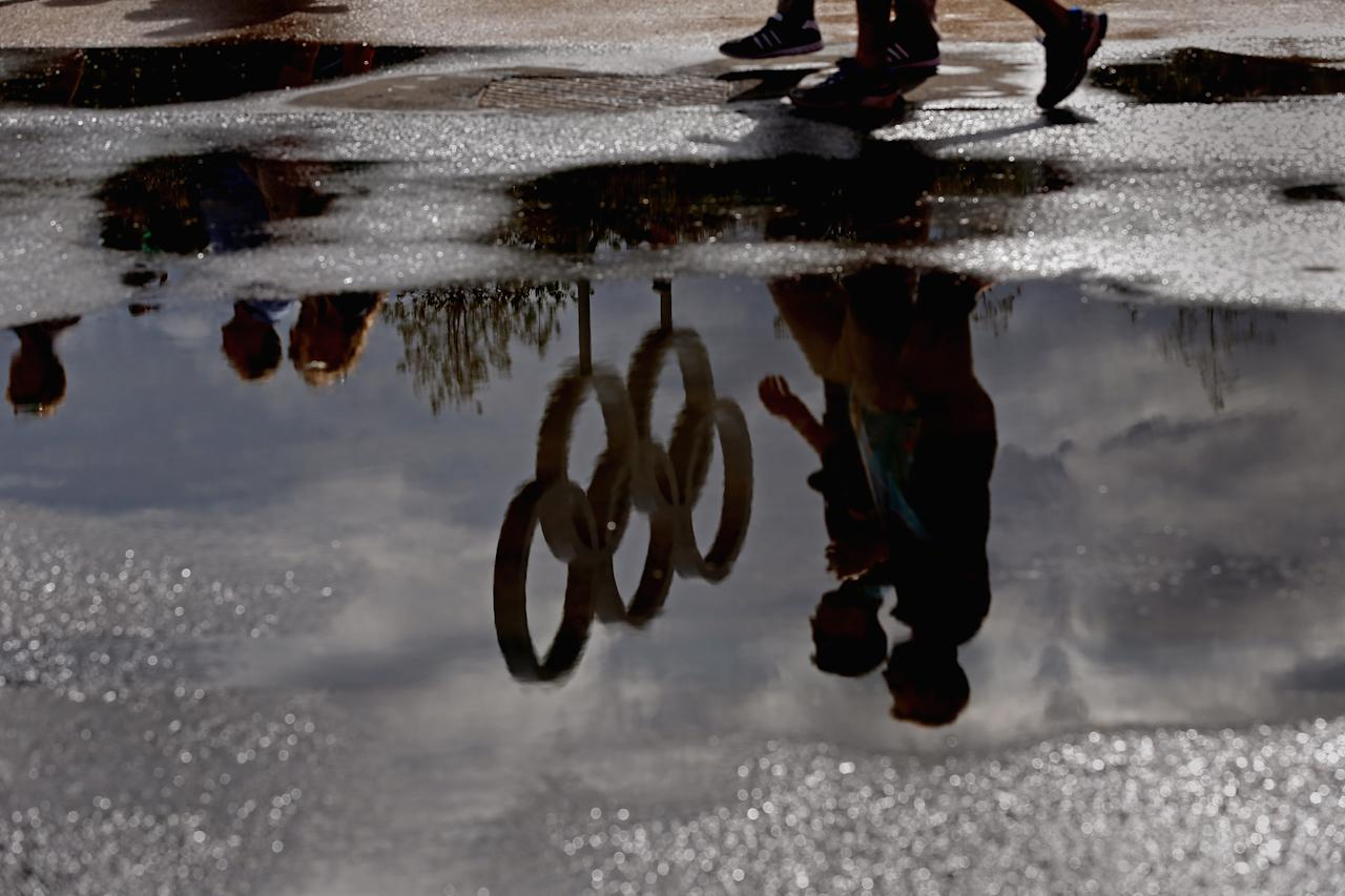 LONDON, ENGLAND - JULY 29:  The Olympic Rings are reflected in a puddle in the Olympic Park on Day 2 of the London 2012 Olympic Games on July 29, 2012 in London, England.  (Photo by Jeff J Mitchell/Getty Images)