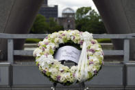 Flowers offered by International Olympic Committee President Thomas Bach are placed at Hiroshima Memorial Cenotaph during his visit Friday, July 16, 2021, in Hiroshima, western Japan. (AP Photo/Eugene Hoshiko, Pool)