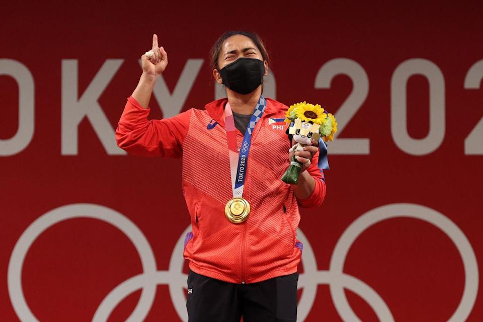 """Gold medalist Hidilyn Diaz of Team Philippines poses with the gold medal during the medal ceremony for the Weightlifting - Women's 55kg Group A on day three of the Tokyo 2020 Olympic Games at Tokyo International Forum on July 26, 2021 in Tokyo, Japan.<span class=""""copyright"""">Chris Graythen—Getty Images</span>"""