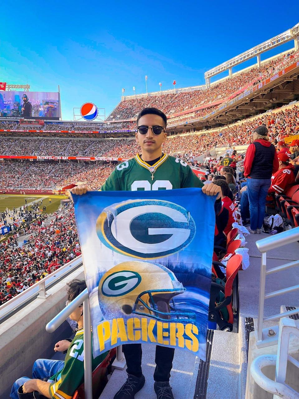 Nelson A. Liborio poses with his Packers flag at Levi's Stadium in San Francisco on Sept. 26, 2021. His post to Twitter displaying calm when the 49ers went up with 37 seconds left went viral after the Packers stormed back to win.
