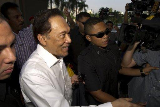 Malaysian opposition leader Anwar Ibrahim (C) arrives to appear before the court in Kuala Lumpur. Anwar and two other defendants from his opposition party were charged with violating a controversial new law governing public gatherings and a court order that banned the April 28 rally from the centre of the capital Kuala Lumpur