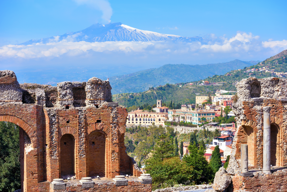<p>A spectacular hilltop locale exuding medieval charm, Taormina is Sicily's seductive summer hotspot. The Greek and Roman influences on its history make this city one of Italy's most picturesque locations–one that's attracted the likes of Oscar Wilde, Woody Allen, and even Elizabeth Taylor. </p><p>An underrated view often overlooked for other Italian hotspots is that of Teatro Antico, where the crystalline waters of the Ionian Sea and the distant smoking cone of Italy's most active volcano, Mount Etna, create a jaw dropping take on Taormina. The theater is still in use, often hosting festivals, concerts, and plays, which makes this vantage point even more culturally immersive. After an afternoon exploring this impressive archeological location, wandering the streets of Taormina is just as captivating as seeing it from above.</p>