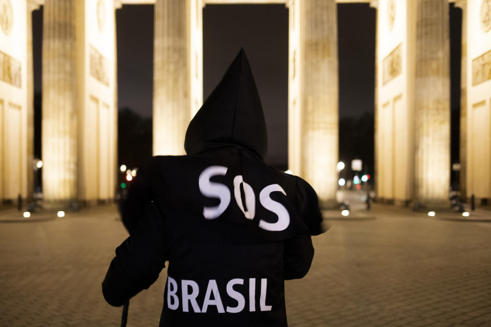 Brazilian activist and artist Rafael Puetter, dressed as the grim reaper, walks in front of the Brandenburg Gate in a one-man protest through Berlin, Germany, early Wednesday, April 7, 2021. The multimedia artist starts his performance at the Brazilian embassy in Berlin at midnight every night to protest against Brazil's COVID-19 policies. Rafael Puetter walks to the Brandenburg Gate and then to the nearby German parliament building, in front of which he counts out a sunflower seed to represent each of the lives that were lost over the past 24 hours in Brazil because of the coronavirus pandemic. (AP Photo/Markus Schreiber)