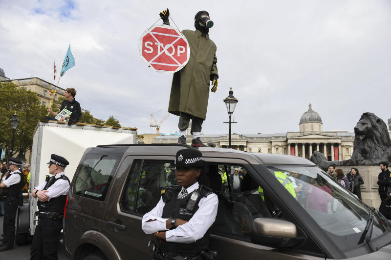 A climate activist stands on the roof of a car during an Extinction Rebellion Protest in London, Monday, Oct. 7, 2019. (Photo: Alberto Pezzali/AP)