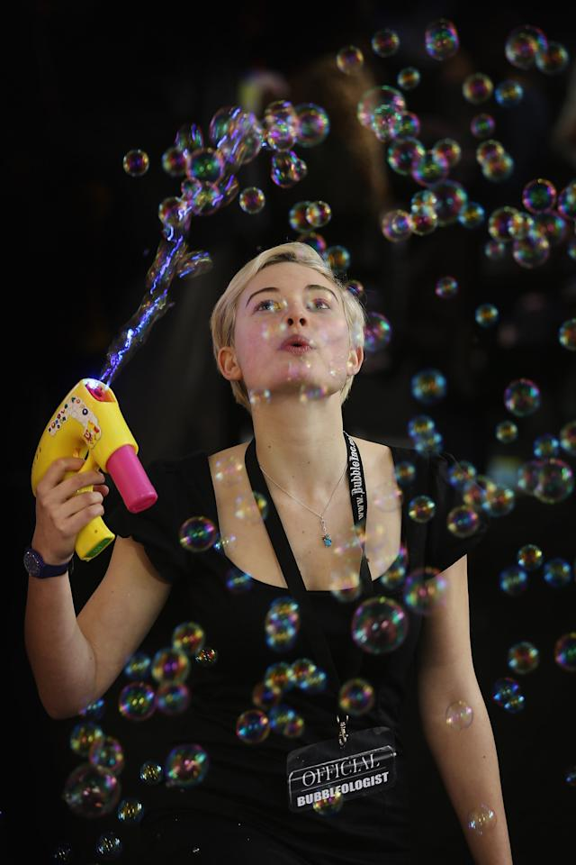 LONDON, ENGLAND - JANUARY 22:  A woman on a trade stand blows bubbles during the 2013 London Toy Fair at Olympia Exhibition Centre on January 22, 2013 in London, England. The annual fair which is organised by the British Toy and Hobby Association, brings together toy manufacturers and retailers from around the world.  (Photo by Dan Kitwood/Getty Images)