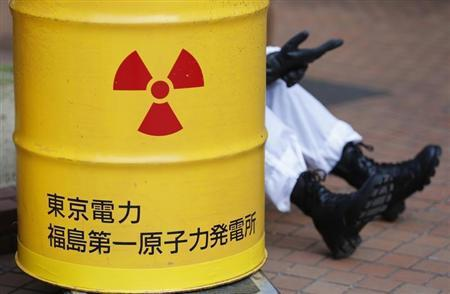 An anti-nuclear protester wearing a protective suit is seen behind a mock drum which is labelled as radioactive waste from Tokyo Electric Power Co's (TEPCO) Fukushima nuclear power plant, before he starts marching in Tokyo March 9, 2014. REUTERS/Yuya Shino