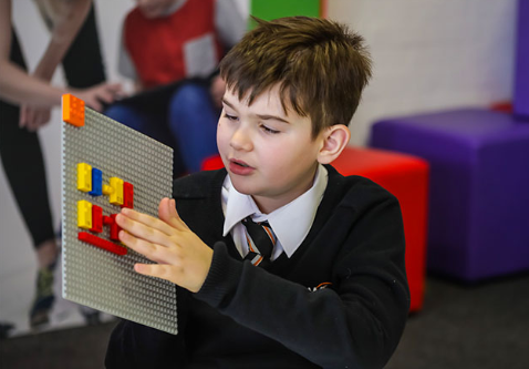 Photo of visually impaired child with LEGO's new Braille bricks.