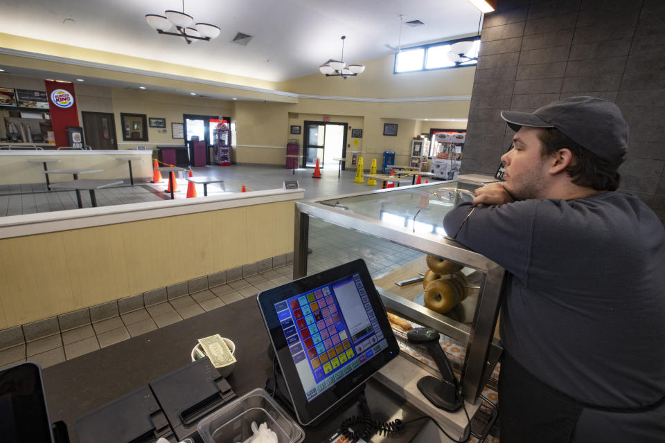 An employee at Dunkin' rests his eyes for a moment as he awaits to-go orders at the empty food court in Bridgewater, MA at 4:30 p.m. on March 16, 2020. Orders in the fast-food restaurants are take-out only as Governor Charlie Baker ordered all sit-down restaurants and bars to close their doors to prevent the spread of coronavirus. (Photo by Stan Grossfeld/The Boston Globe via Getty Images)