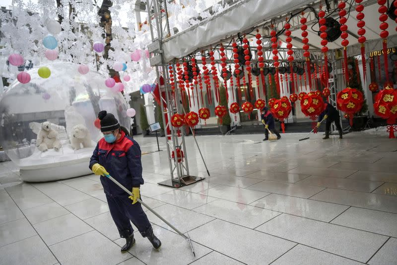 Worker wearing a face mask cleans the ground of a food court amid snowfall on Valentine's Day at the Sanlitun shopping area