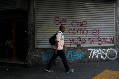 """A man walks past a mural that reads, """"It's falling like the Berlin Wall"""" during a blackout in Caracas, Venezuela March 27, 2019. REUTERS/Carlos Garcia Rawlins"""
