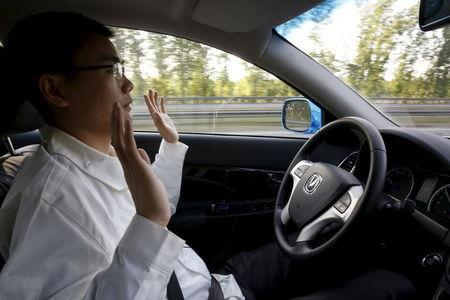 Li Zengwen, a development engineer at Changan Automobile, lifts his hands off the steering wheel as the car is on self-driving mode during a test drive on a highway in Beijing, China, April 16, 2016. REUTERS/Kim Kyung-Hoon