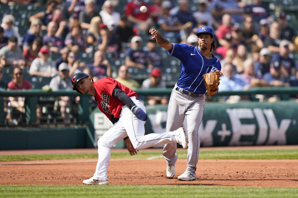 Kansas City Royals' Adalberto Mondesi, right, throws out Cleveland Indians' Myles Straw at first base as Andres Gimenez runs by in the second inning of a baseball game, Monday, Sept. 27, 2021, in Cleveland. (AP Photo/Tony Dejak)